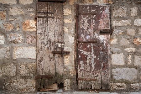 Locked ancient wooden doors in gray stone wall. Perast town, Montenegro photo
