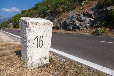 in stone: White kilometer stone post on the roadside in Montenegro