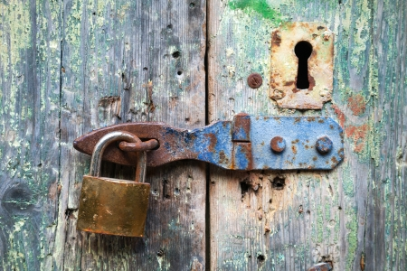 Old lock and rusted keyhole on green wooden door photo