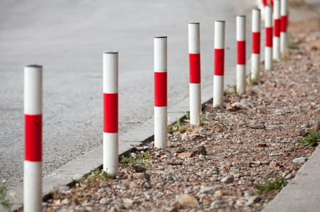 Striped red and white signal poles stand on asphalt roadside photo