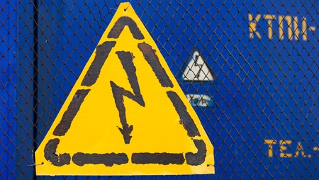 rabitz: High voltage yellow sign mounted on blue metal rabitz grid with blue metal wall on background