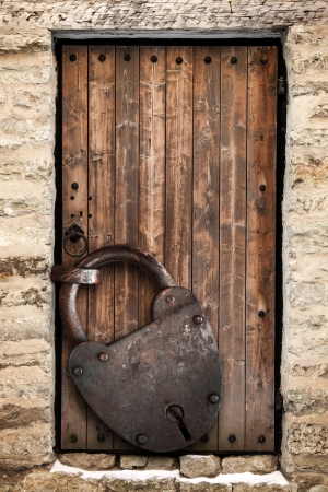 Ancient locked wooden door and big rusted padlock, old fashioned safety concept photo