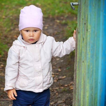 brown  eyed: Brown eyed baby girl in pink hat opens old green wooden wicket Stock Photo