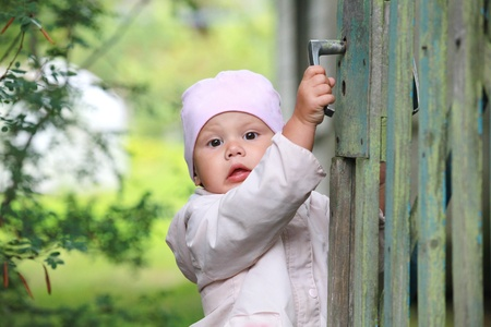 brown  eyed: Brown eyed baby girl in pink plays with old green wooden wicket