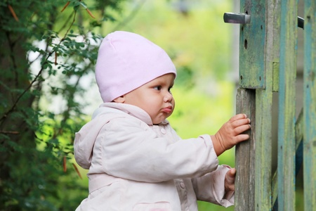 wicket door: Baby girl in pink hat plays with old green wooden wicket