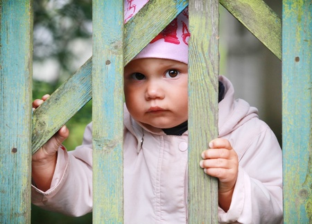 wicket door: Brown eyed baby girl in pink hat plays with old green wooden wicket Stock Photo