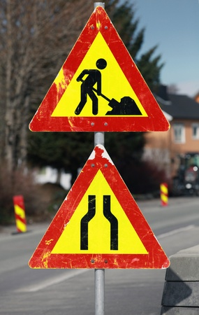 roadwork: Under construction and Road narrows road signs on one pole