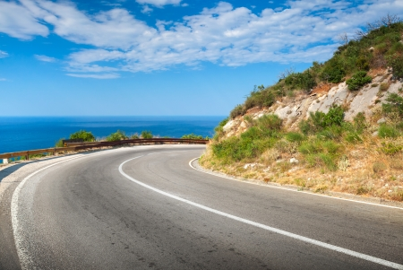 Turn of mountain asphalt road with blue sky and sea on a background photo