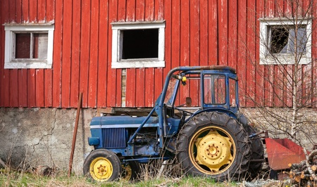Small blue tractor stands on grass nearby red barn wall in Norway photo