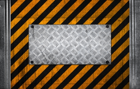Metal panel on black and yellow striped caution pattern of industrial concrete wall photo