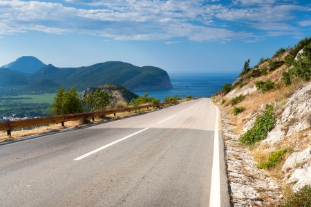 Mountain road with blue cloudy sky and sea on a background. Adriatic sea coast, Montenegro photo