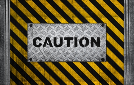 Caution label metal panel on black and yellow striped pattern of industrial concrete wall photo