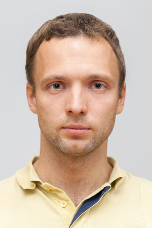 Closeup studio face portrait of young Caucasian ordinary man isolated on gray background photo