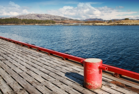 Red mooring bollard on the pier in Norway Stock Photo