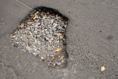pot hole: Pothole with gravel on damaged urban asphalt road