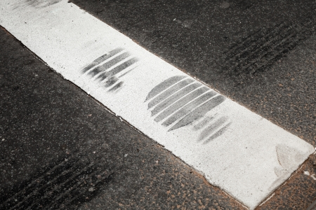 Pedestrian crossing fragment with white stripe and tire track on asphalt road photo