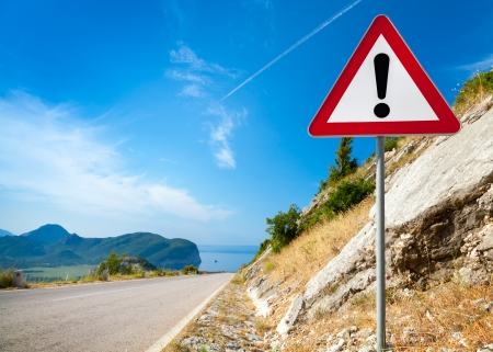 Warning road sign with an exclamation mark in red triangle on mountain highway Фото со стока