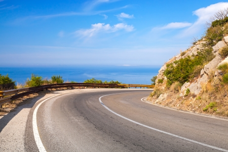 curve road: Turn of mountain highway with blue sky and sea on a background Stock Photo