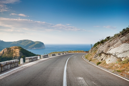 Right turn of mountain highway with blue sky and sea on a background photo