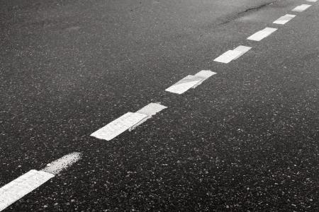 scheidingslijnen: Donkere natte asfalt weg achtergrond met gestreepte scheidslijn markering lijn Stockfoto