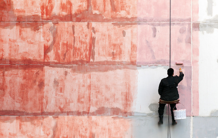 priming: Painter works on the outer building wall with red priming paint