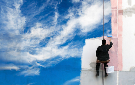 Painter paints bright blue sky on the urban wall photo