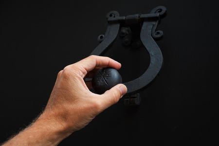 doorknocker: Male hand knocking old black metal door