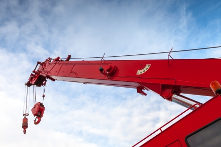 mobile crane: Red truck crane boom with hooks and scale weight above blue sky Stock Photo