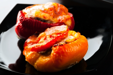 Stuffed bell peppers with chopped meat, cheese and tomato lay on black plate photo