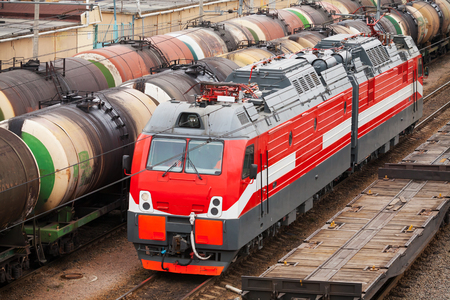 Modern red diesel electric locomotive rides on railway tracks with freight coaches photo
