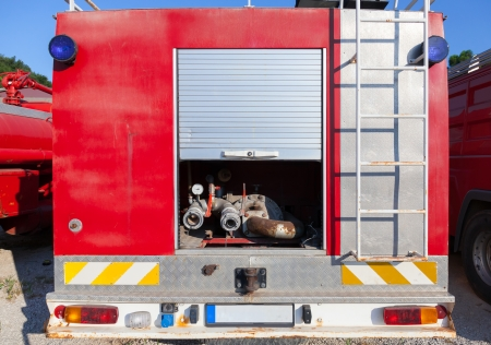 The rear of fire truck with water pump equipment photo