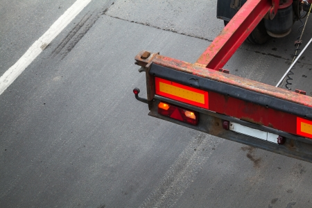 Back part with taillight of empty truck cargo trailer on the asphalt road photo