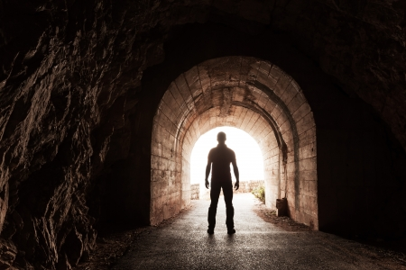 Young man stands in dark concrete tunnel and looks out in the glowing end Stock Photo