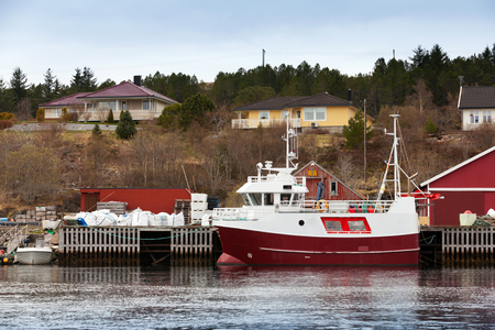 Small red and white fishing boat stands moored in Norway coastal town photo
