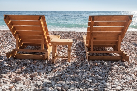 Two wooden sun loungers stand on the Adriatic Sea beach in Montenegro photo