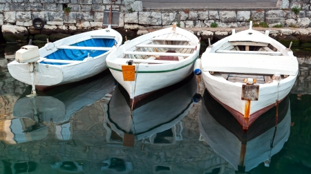 Three white wooden fishing boats stay moored in Perast town, Montenegro photo