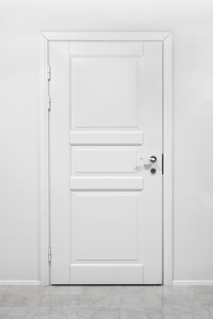 Classical cerró la puerta de madera en la pared blanca de la oficina Foto de archivo