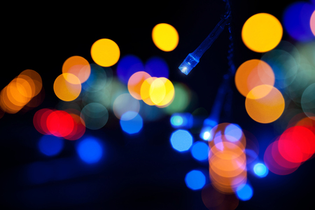 Colorful LED (light emitting diodes) lights garland with bokeh effect on black background photo