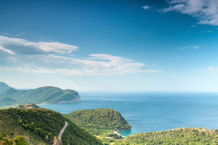 Adriatic sea landscape with blue cloudy sky and green coastal mountains. Montenegro photo