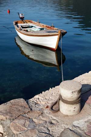 White wooden fishing boat floats moored in Perast town, Montenegro photo