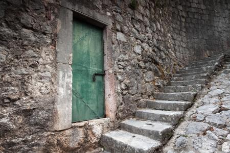 Oude gesloten groene deur en stenen trap in Perast stad, Montenegro