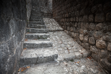 Old stone stairway goes up on the street of Perast town, Montenegro photo