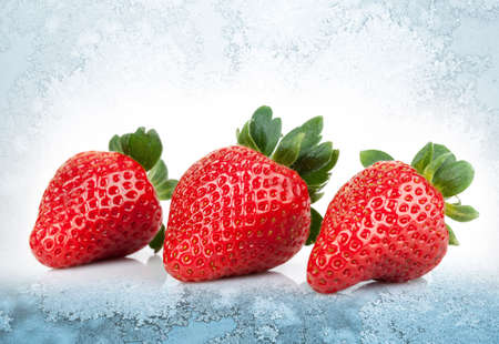 Three fresh strawberries lay on blue ice background photo