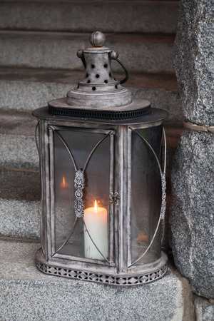 Old metal outdoor lamp with burning candle stands on stone stairs photo