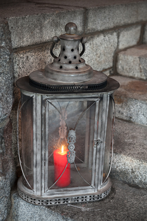Old metal outdoor lamp with red burning candle stands on stone stairs photo