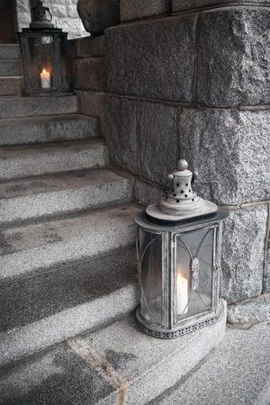 Old metal outdoor lamps with burning candles stands on stone stairs photo