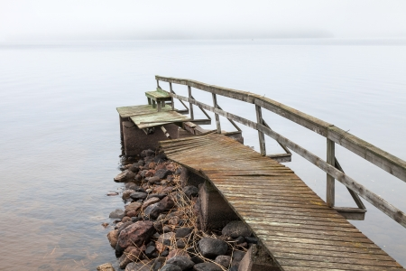 Old ruined wooden pier on the lake in foggy morning photo