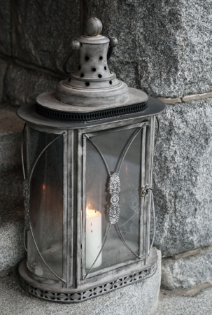 Old metal lamp with burning candle stands on stone stairs photo