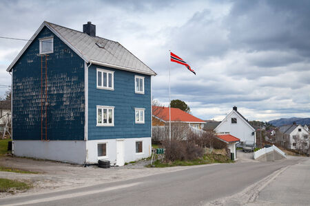 Small Norwegian village landscape with colorful wooden houses and flag photo