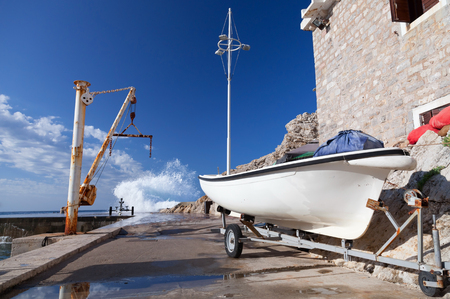 White fishing boat and small crane. Embankment of Petrovac town, Montenegro photo